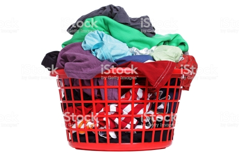 Colorful clothes in a red laundry basket on white background