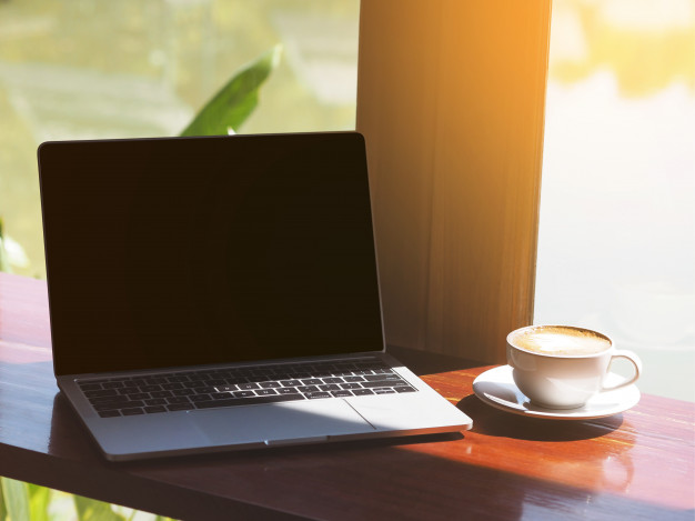 white-cup-coffee-cappuccino-laptop-computer-table-beside-glass-window_42414-328